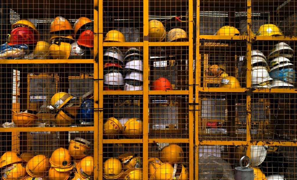 Safety hats stored inside a caged locker: training a new generation of warehouse workers