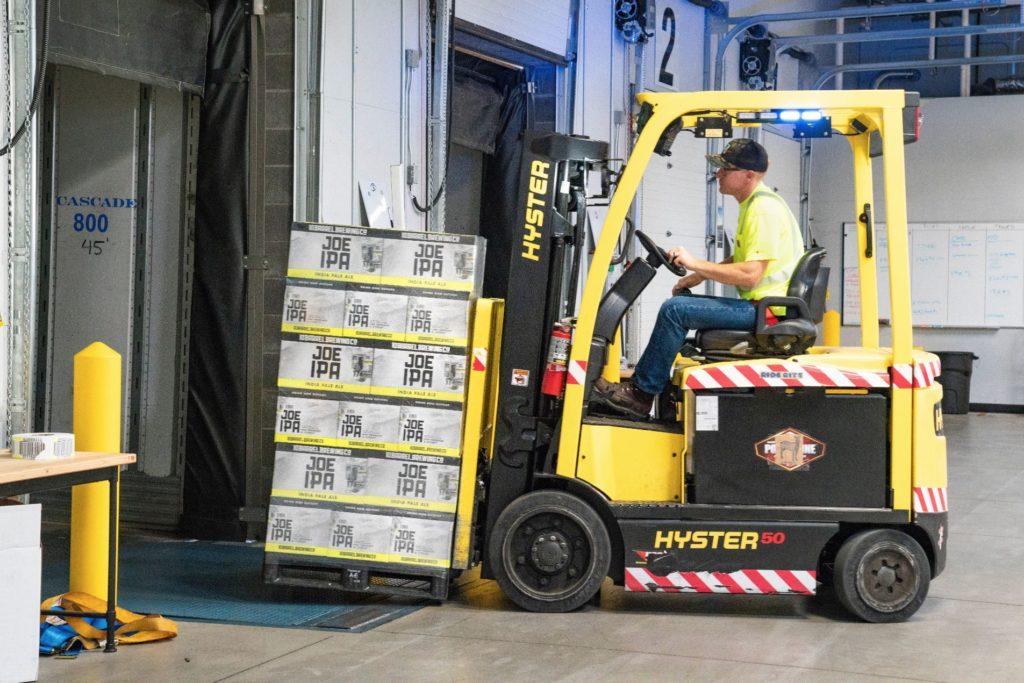 A logistics warehouse worker training & driving forklift